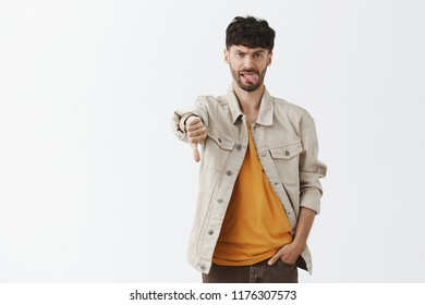 This party sucks, dislike. Displeased childish and emotive handsome modern male with beard in shirt over yellow t-shirt holding hand in pocket, showing thumb down, sticking out tongue from displeasure