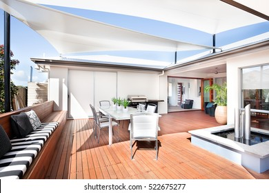 This patio area has a wooden floor and a long bench attached to it, there are some small mattresses and pillows on it. A white table and chairs are under the creative roof design,