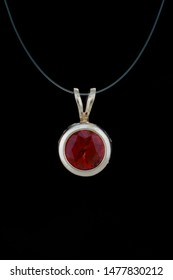 In this pendant a 6mm round faceted red sunstone is bezel set in white gold and hangs from a white gold cable chain. The pendant is shown against a black background.