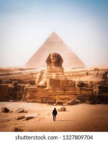This photo depicts a man standing in front of great pyramids of giza and ephinix.