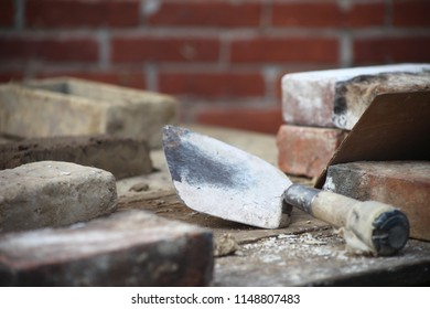 This photo depicts the work of a bricklayer. This bricklaying image includes a trowel, mortar, and cement, along with bricks. The job of laying bricks takes special skill.