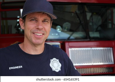 This is a photo of a fireman standing in front of a fire engine.