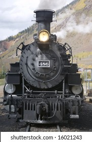 This is a photo of the front of an old steam locomotive getting ready to pull a group of passenger cars through the mountains of Colorado.