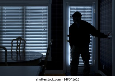 This photo illustrates a burglary or thief breaking into a home at night through a back door. View from inside the residence.