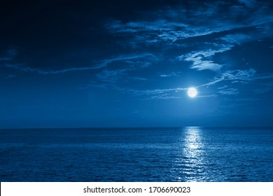 This photo illustration of a deep blue moonlit ocean and sky at night  would make a great travel background for any travel or vacation purpose. - Shutterstock ID 1706690023