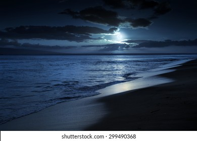 This photo illustration depicts a quiet and romantic moonlit beach in Maui Hawaii. It could represent any beach at night with calm waves and cloud filled night time sky.