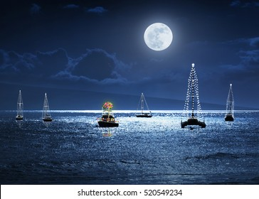 This photo illustration depicts a warm weather Christmas Holiday with deep blue sky and ocean at night, a full moon and a small group of boats decorated with lights. A Palm Tree as a Christmas Tree.