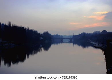 This is a photo the main river in Torino, Italy. Beside the river has trees and building. It is such a nice and beautiful view.