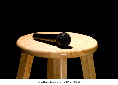 This is a photo of a microphone sitting on top of a wooden stool lite from above. Shot on a black background.