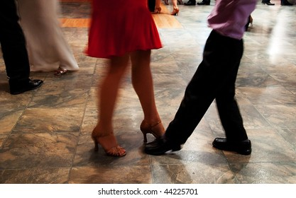 This photo shows a woman in high heels and skirt teaching a young boy how to dance, it's filled with motion as they are ballroom dancing.
