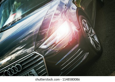 This photo was taken in Derby, Derbyshire / United Kingdom - May 27, 2018: A black Audi A4 saloon car with bright headlights.