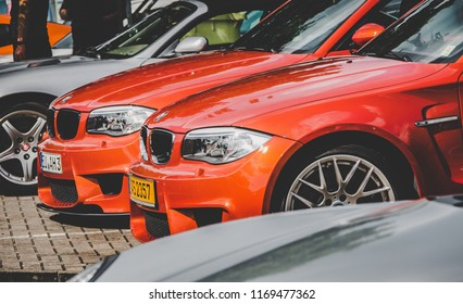 This photo was taken in Nurburgring / Germany - August, 3rd 2014: A couple of orange BMW 1 Series M coupe sports cars