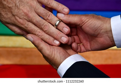In this photo we see a silver wedding band being slipped on the hand of a man by another man with the lgtbq rainbow in the background. So  simple , yet so clear.