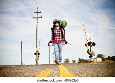 This is a photo of a young man with a beard hitchhiking.