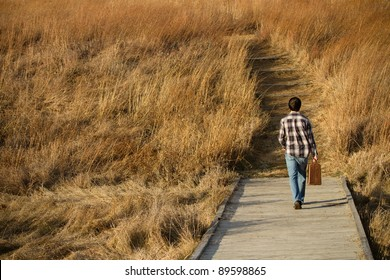 This is a photo of a young man walking down a path with a suitcase.