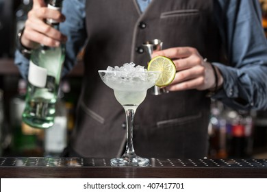 This is a photograph of barman serving cocktail.