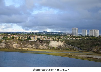 This is a photograph of beautiful Back Bay Newport Beach, California, United States of America. In the background of the photo you can see the Fashion Island outdoor mall.