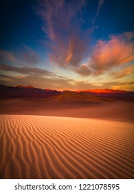 This is a photograph of Death Valley sand dune with colorful clouds in California, USA