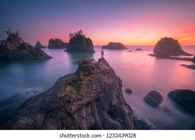 This is a photograph of a man standing on top of seastack and watching sunset of Oregon coast.