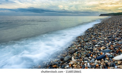 This photograph was taken in Hualien, Taiwan. It is a famous pebble beach. One can see heaps of pebbles of different colors, shapes and sizes. The clouds and dramatic weather create a dramatic feel.