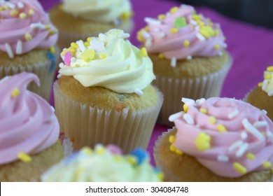 This is a photograph of Vanilla cupcakes topped with Pink and Yellow Buttercream, and colorful sprinkles