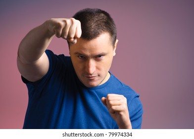 This is a photograph of a young man standing in a boxing position