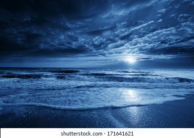 This is a photographic illustration of a beautiful midnight blue ocean moonrise along the coast with dramatic sky and rolling waves.