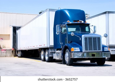 This is a picture of 18 wheeler semi truck loading at a warehouse building.