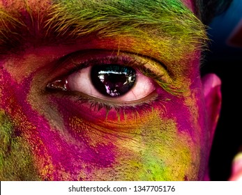 This is the picture of a male. picture shows the colourfull eye during holi festival which is celebrated in India by the huge amount of people of India.the eye looks very beautiful.