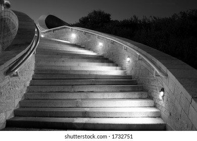 This picture is a night shot of concrete stairs while lights illuminate the direction to follow.