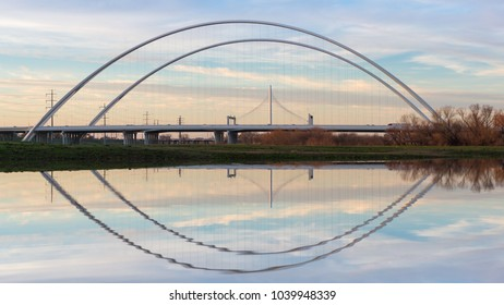 This is the picture of Reflection of Margaret Hunt Hill Bridge and Margaret McDermott Bridge during Day time from Trinity River, Dallas, Texas.