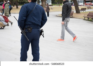 This picture is showing a japanese police in an uniform and his gear can be seen clearly in the picture. Few people can be seen in the picture.