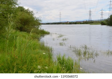This picture shows a riverside with high-voltage power line columns on the background
