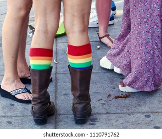This is a picture of a small group of women engrossed in conversation.  What has caught my eye  is someone wearing low leather boots with bright rainbow knee-highs pulled up high out of the boot.