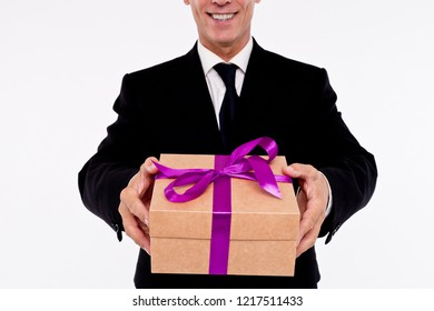 This present is for you! Part of man in suit showing present box with smile while standing against white background