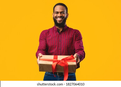This Present Is For You. Young african man holding gift box giving it to camera isolated over yellow studio wall