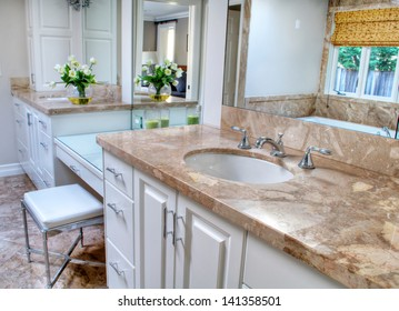 This is a pretty and contemporary bathroom with large vanity and sink areas in neutral colors.  Floor is a marble and cabinets a shade of white.
