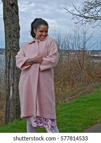 This pretty multi-ethnic woman is in a playful pose wearing a long pastel pink coat outdoors on an early spring day.  Photo is vertical orientation.