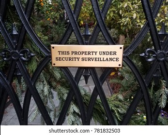 this property under security surveillance sign on black metal fence