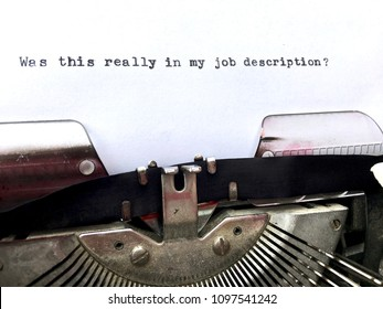 Was this really in my job description? Phrase typed in black ink on white paper on vintage retro typewriter machine