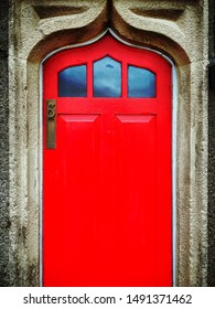 This red door is part of an old Irish cottage in Ireland.  The arabesque shape of the door and frame accents the bright red door.