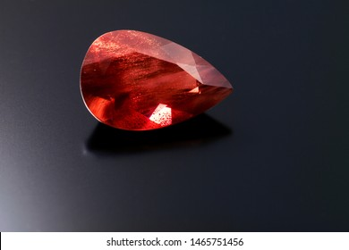 This red orange colored pear cut sunstone sits on a black reflective background and shows strong shilling.