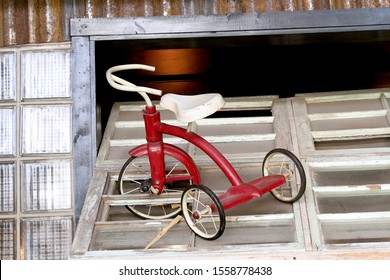 This retro looking children's tricycle is sitting on top of a window.  The front tire is through a broken section of glass.  It is set in a retro looking background.