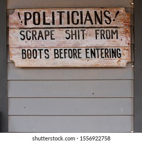 This is a retro looking political sign showing that politicians needed to scrape the shit from their boots before entering.  There is space below the sign to put a shady politician`s face.