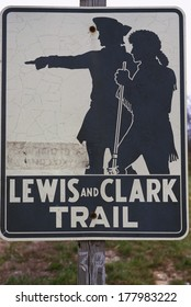 This is a road sign that marks the Lewis and Clark Trail. There is a silhouetted graphic on the sign of the explorers, Lewis and Clark against a white background.
