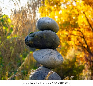 This rock cairn is a symbol of meditation, contemplation, and natural beauty on a golden autumn day. Although the spacing in this cairn appears random, the rock stack is nevertheless balanced.