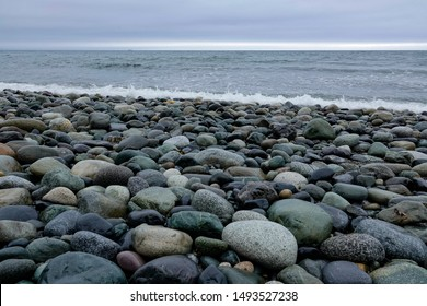 This rocky beach on Puget Sound is very difficult to walk on.  The tide is out revealing the smooth and beautifully colored stones.  Low angle with level horizon at top third.  It is a cloudy day.