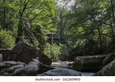 This is a round house back in the woods and on a rocky creek of Balsam grove, NC.