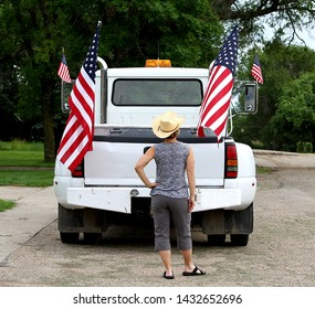 This rural woman is wearing a cowboy hat and looking at United States of America (USA) flags hanging off of a truck.  The pick up truck is white and has four flags visible.