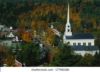 This is Scenic Route 100 in the autumn. There is a large white New England style church with a tall steeple next to smaller buildings of the town.